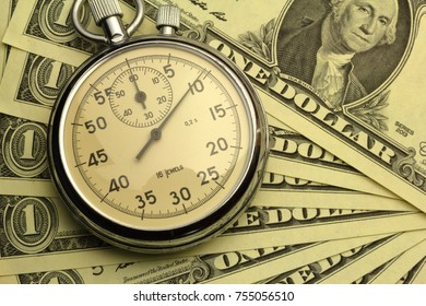 Time and Money - US Dollar notes and a stopwatch
