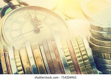 Time is money, time value of money concept : Coins and vintage brass pocket watch, ideas of time which is a valuable commodity or resource, money today is worth more than the same amount in the future