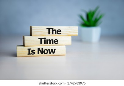 The time is now - words from wooden blocks with letters, the time is now concept, top background.