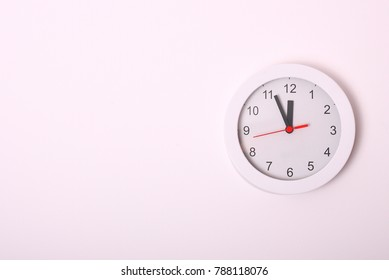 Time on circle clock on white wall background.