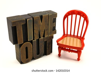 Time out chair child discipline concept with vintage letter press letters and red chair.