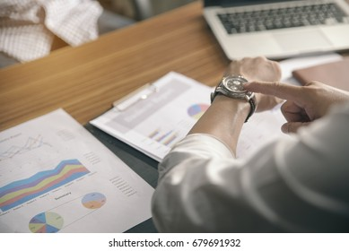 Time out concept.Business man seeing wrist watch to check time at office.Boss look at clock to work.On Wooden desk with calendar,laptop,annual and summary report.It's Time out for appointment meeting.