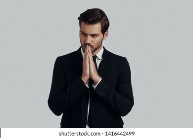 Time to overthink everything. Handsome young man in full suit keeping hands clasped while standing against grey background