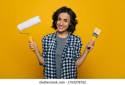 Time to paint. Half-length photo of a smiling nice girl, in a black and white checkered shirt, holding a paint roller in her right hand and a brush in her left hand.