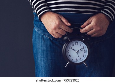 Time is passing or biological clock, female hand holding stylish black vintage alarm clock, selective focus. Concept of reproductive health control for women.