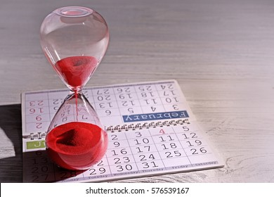 Time passing concept. Crystal hourglass with red sand and calendar on light wooden background
