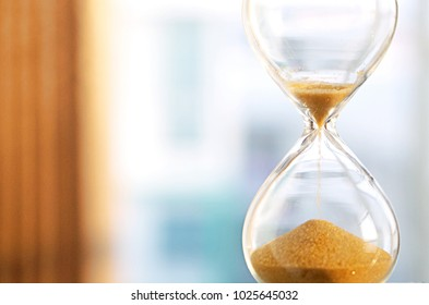 Time passing concept,urgency and running out of time. Sand fall in hourglass