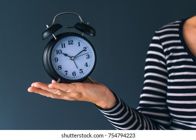 Time is passing, female hand holding stylish black vintage alarm clock, selective focus