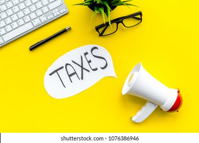 Time to pay taxes. Taxes day concept. Announcement or notification about taxes. Megaphone near cloud with word taxes on yellow background top view