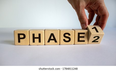 Time for Phase 2. Hand is turning a cube and changes the word 'Phase 1' to 'Phase 2'. Beautiful white background. Business concept. Copy space.