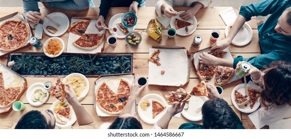 Time for pizza. Top view of young people in casual wear picking pizza while having a dinner party indoors
