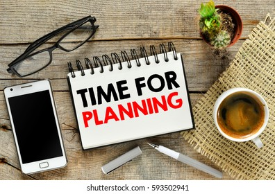 Time for planning concept. Smartphone notebook and coffee on wooden background