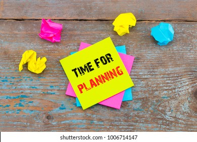 Time for planning -  on sticky note with crumpled papers on wooden background.