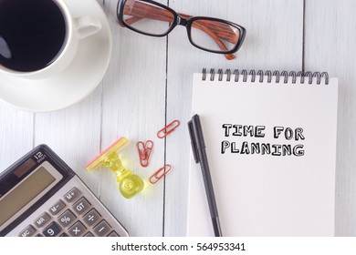 TIME FOR PLANNING text on notebook.coffee,calculator,pen,rubber stamp,glasses on the desk.top view.