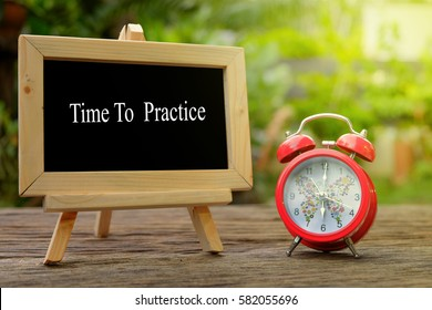TIME TO PRACTICE! inscription written on chalkboard and red alarm clock on  old wooden desk . Time concept.