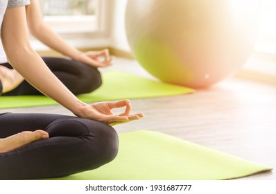 Time for practicing yoga. Two youngs attractive women sitting in Ardha Padmasana exercise, Lotus pose on meditation, closed eyes, wearing sportswear on mat at home. lifestyle concept