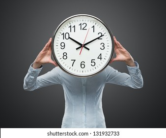 Time pressure, close up of young businesswoman covering her face with analog clock isolated on gray background
