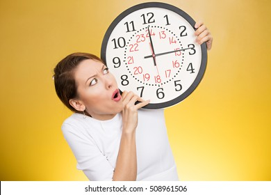Time pressure. Stressed woman holding clock looking anxiously running out of time isolated on yellow background. Human face expression emotion reaction. Last moment