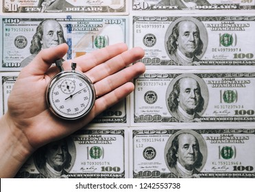 Time for quick money. Woman's hand holding a grey stopwatch over dollars background. Credit concept. Usurer.