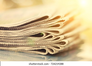 Time to read concept. Newspapers folded and stacked on the blue surface and blur background. Closeup, selective focus, sunlight.