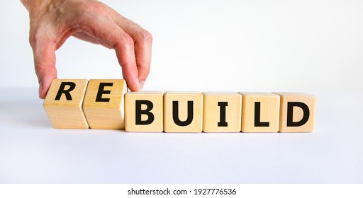 Time to rebuild symbol. Businessman turns wooden cubes and changes the word 'build' to 'rebuild'. Beautiful white background. Business, build or rebuild concept. Copy space.