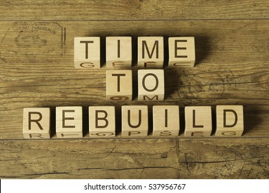 time to rebuild text on wooden cubes on a wooden background