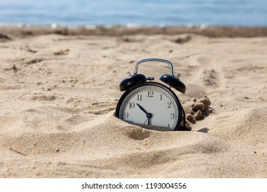 Time to relax! The alarm clock on the sand shore of the sea.