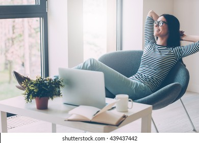 Time to relax. Cheerful young beautiful woman keeping hands behind head and looking through a window with smile while sitting at her working place