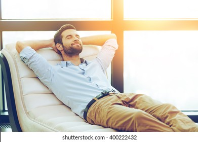 Time to relax. Handsome young man holding hands behind head while sleeping on the couch
