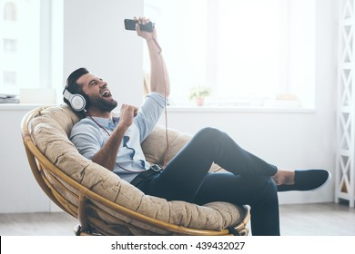 Time to relax. Handsome young man in headphones gesturing and keeping eyes closed while sitting in big comfortable chair at home
