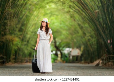 Time to Relax, Happy traveler asian woman with suitcase standing in the middle of Bamboo grove, Tunnel bamboo trees and walkway, Face looking up and Smiling. Travel lifestyle concept. Copy space