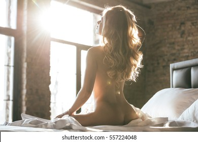 Time to relax. Rear view of sexy young woman sitting on her bed at home