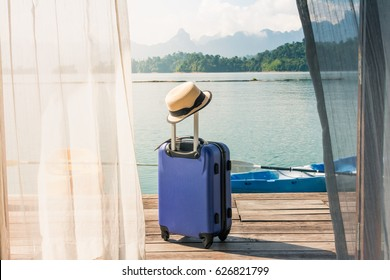 Time to Relax, traveling suitcase with hat standing on the floor out the room, travel lifestyle concept.