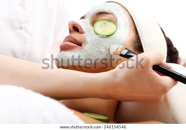 Time to relax, the woman at day spa salon. Cosmetic procedure woman's face in the mask mitigating and cucumber slices on eyes