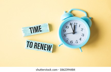 Time to renew , text in a gold frame on a pink background, near an alarm clock. Business, strategies, plans and goals concepts.