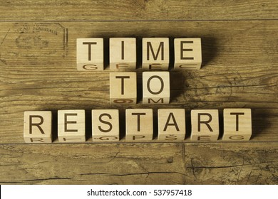 time to restart text on wooden cubes on a wooden background