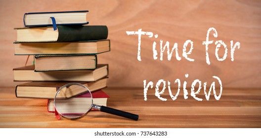 Time for review text on white background against magnifying glass with stack of books on table