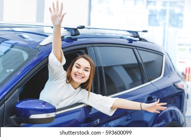 Time for the ride! Beautiful young excited woman smiling joyfully looking out the car waving her hands happily copyspace purchase buying car consumerism happiness new rental lifestyle youth concept