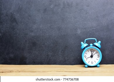 Time is running out concept with classic alarm clock isolated on wooden table and blackboard background