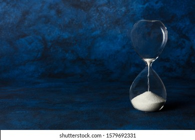 Time is running out concept. An hourglass with oozing sand, on a dark blue background with copyspace