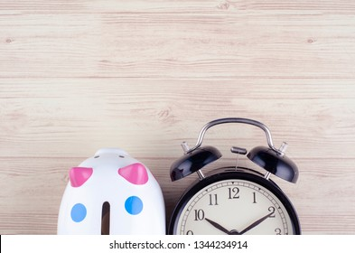 Time for saving money concept, flat lay image of alarm clock and piggy bank  on wooden desk