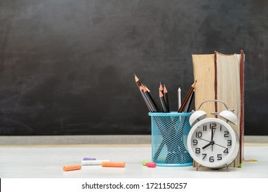 Time to school and education concept. Books with pencil holder on white table. Blackboard in background.
