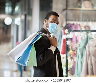 Time to shop at black friday and seasonal sales ahead of holidays during covid-19 pandemic. Young african american guy in protective mask holds multicolor shopping bags near shop window in urban mall