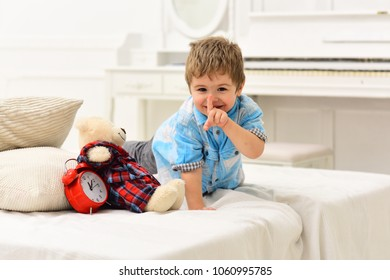 Time to sleep concept. Child in bedroom with silence gesture. Boy with happy face puts favourite toy on bed, time to sleep. Kid put plush bear near pillows and alarm clock, luxury interior background.