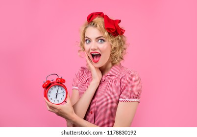 Time. Smiling woman with alarm clock. Surprised woman with alarm clock. Housewife with alarm-clock. Pinup woman in red dress with alarm-clock. Retro style. Makeup. Vintage. Girl with pin-up hairstyle.