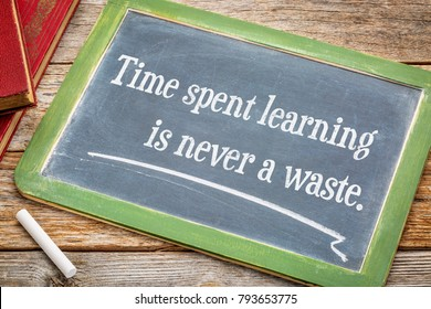 Time spent learning in never a waste - inspiraitonal quote on a slate blackboard with a white chalk and a stack of books against rustic wooden table