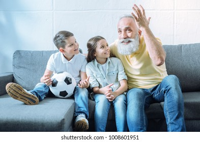 Time for a story. Adorable youngsters smiling cheerfully while sitting on a sofa and looking at their radiant granddad gesturing while telling something exciting.