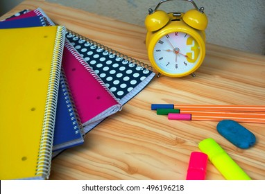 time to study   at the desk with colorful notebooks, calculator, highlighters and a yellow watch