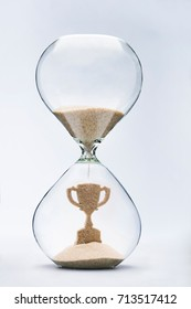 Time is success concept with falling sand taking the shape of a trophy inside a hourglass