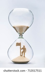 Time is success concept with falling sand taking the shape of a businessman with flag on mountain top inside a hourglass